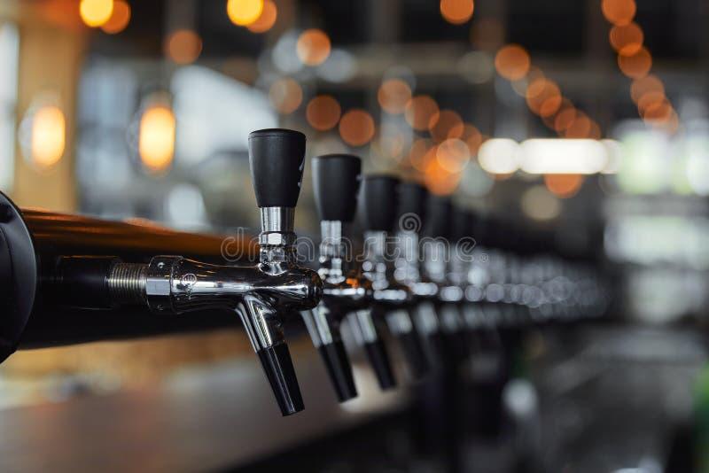 Robinets de bière dans la brasserie en perspective photo stock