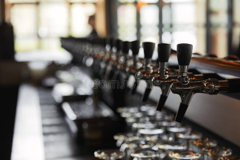 Robinets de bière dans la brasserie en perspective photos stock