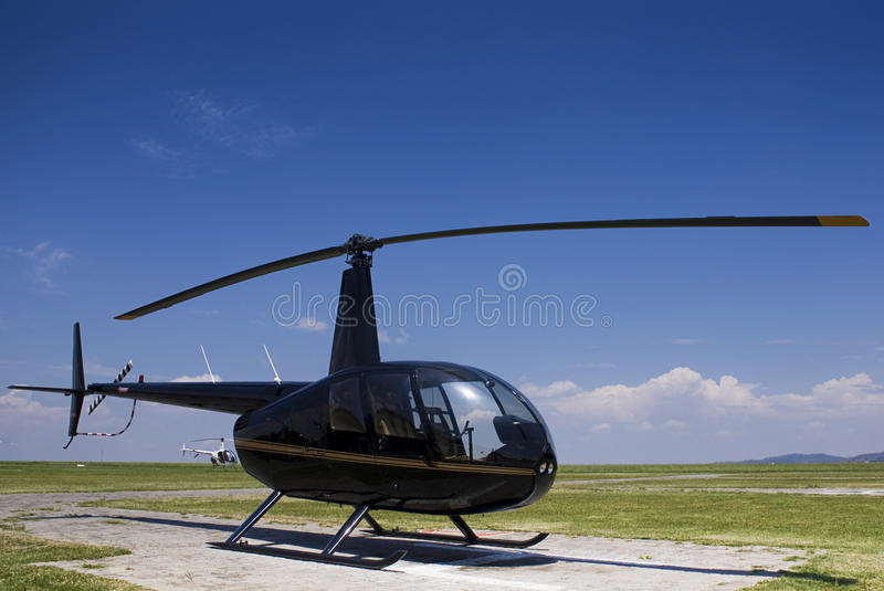 Robinson R44. A four seater light duty, helicopter. Parked on the Helipad. horizontal format alternate, less acute an angle on the aircraft, more blue stock photos
