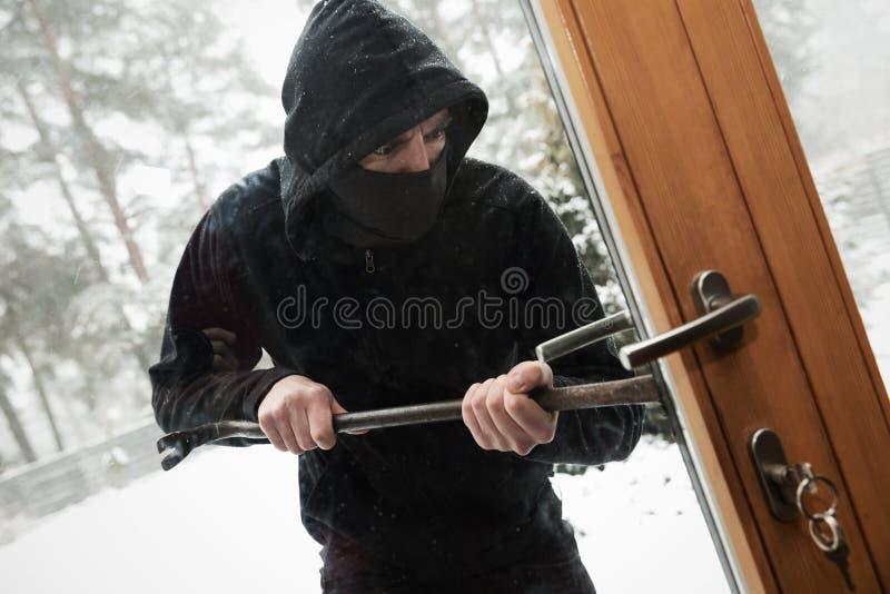 Robo de la casa - ladrón que intenta la puerta abierta con la palanca fotos de archivo