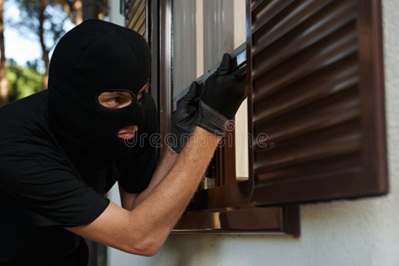 Robo o robo Robo de un apartamento Ladrón en máscara imagenes de archivo