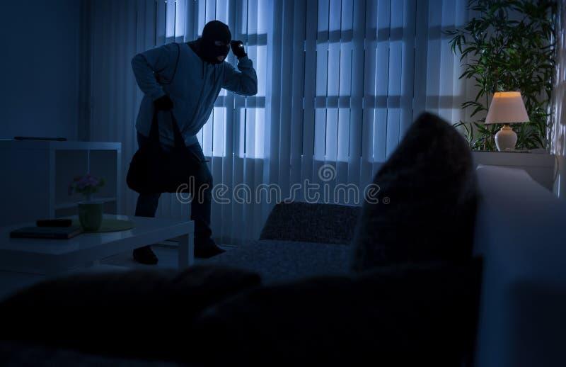 Robo o ladrón que se rompe en un hogar en la noche con una d trasera fotos de archivo