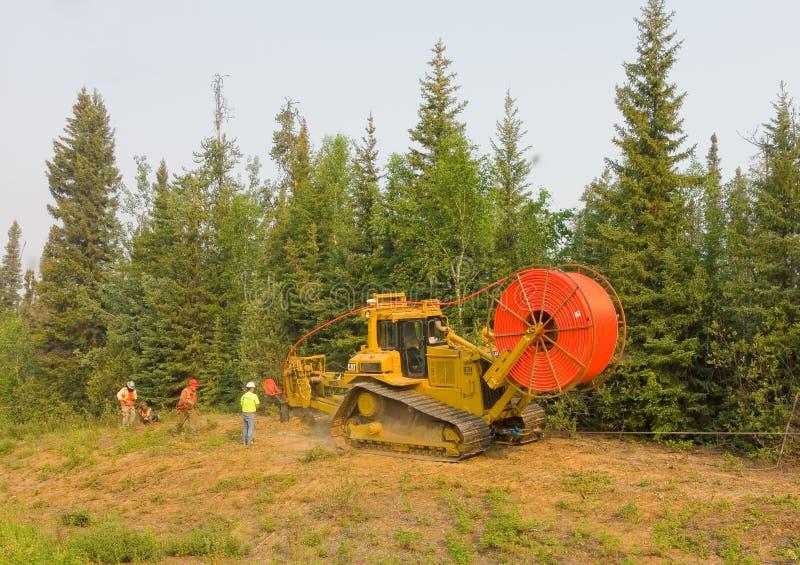 Robociarzi kłaść włókno - wzrokowy kabel w północnych zachodów terytorium obrazy royalty free