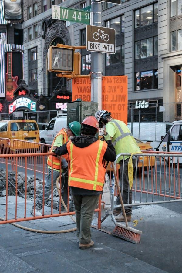 Robociarzi widzieć usuwać stare brukowe cegiełki w Miasto Nowy Jork, usa zdjęcie stock