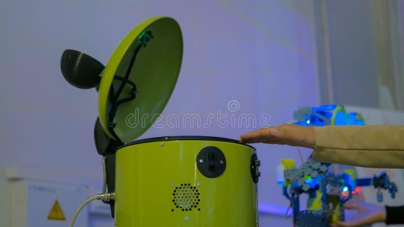 Robot amarillo divertido del cubo que intenta coger la mano de la mujer fotos de archivo