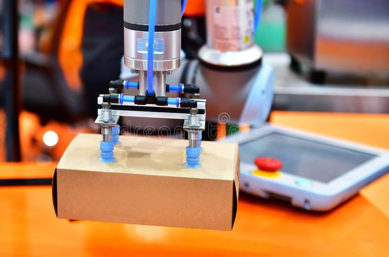 Robot arm arranged product box in factory. Robot arm arranged product box on Automatic industrial machinery equipment in production line factory stock photo