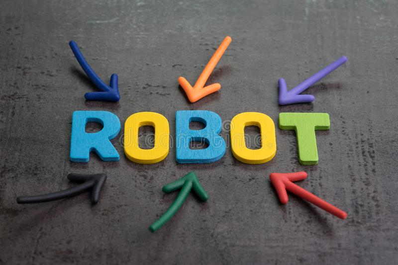 Robot or artificial intelligence concept, multiple arrow pointing to colorful alphabets building the word ROBOT on black cement royalty free stock photos