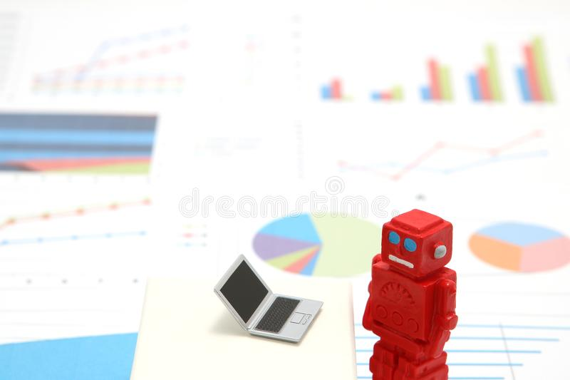 Robot or artificial intelligence and laptop on graphs and charts. Concept of artificial intelligence. royalty free stock photos
