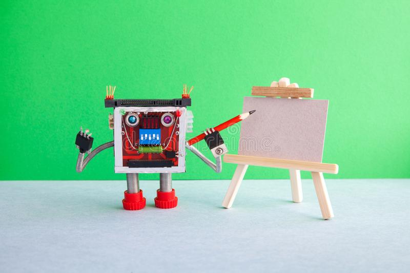 Robot artist begins to create a drawing with a pencil. White paper template, wooden easel. Advertising poster studio. School of visual arts. copy space stock images
