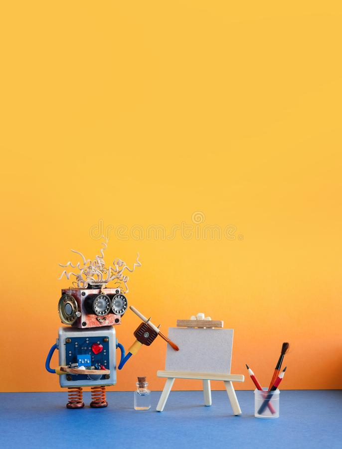 Robot artist begins to paint artwork. Creative robotic character with a watercolor brush, palette, wooden easel . Yellow royalty free stock image