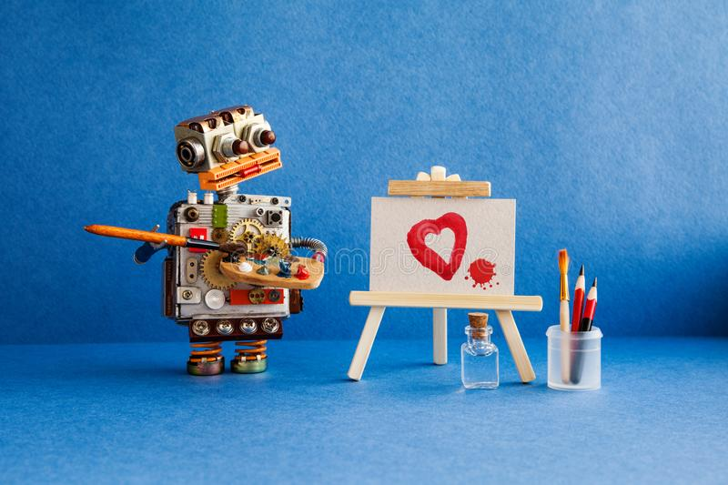 Robot artist with brush in hand looks at the red heart and a blot painted in watercolor on white paper and a wooden. Easel. Advertising poster studio school of stock photo