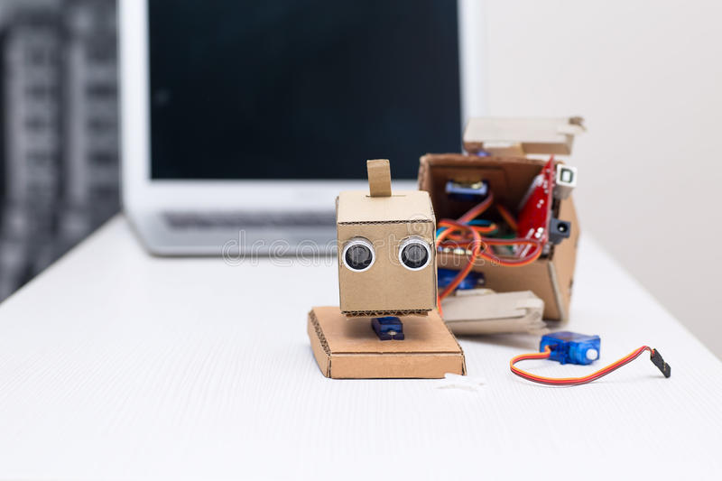 robot in the assembly process on a white table home stock photo