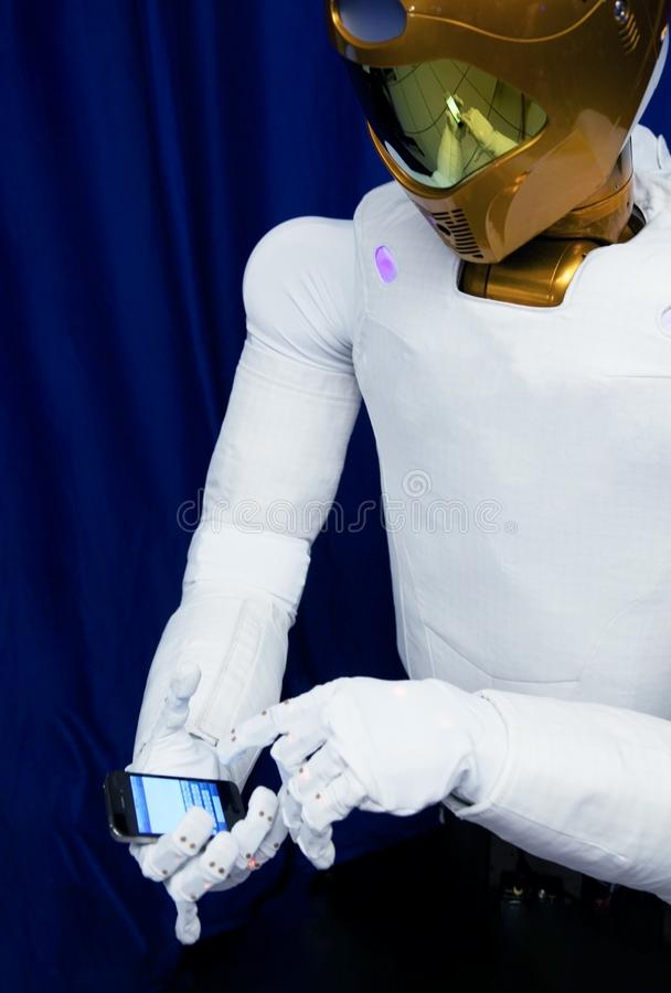 Robot astronaut with a mobile phone in his hands. Elements of this image were furnished by NASA stock image