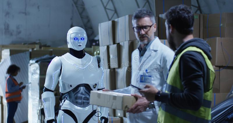 Robot bringing box to technicians in a warehouse. Medium long shot of robot bringing a box to technicians in a warehouse royalty free stock photos