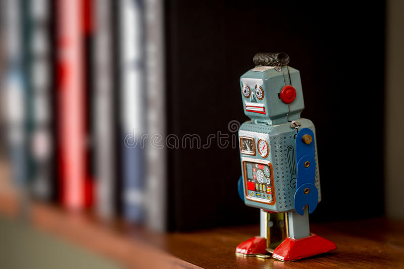 Robot de jouet de bidon de vintage sur des étagères à livres photo libre de droits