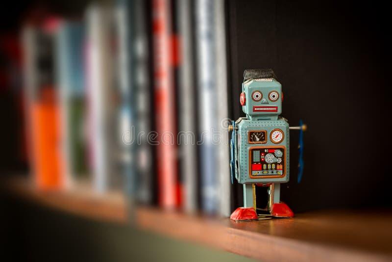 Robot de jouet de bidon de vintage sur des étagères à livres photographie stock libre de droits