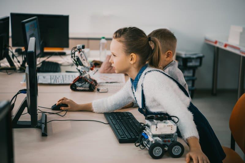 robot de programación adolescente concentrado del niño en el tronco de la clase fotografía de archivo libre de regalías