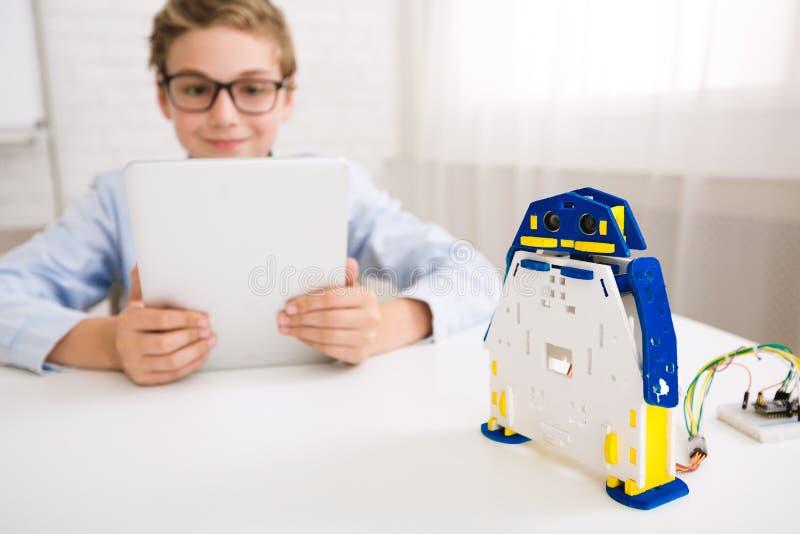 Robot de programación del muchacho con la tableta en clase imágenes de archivo libres de regalías