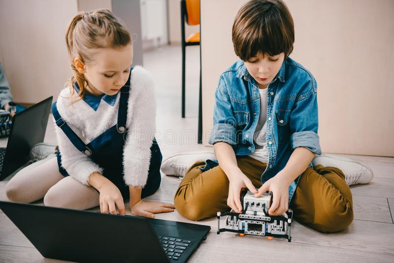 robot de programación enfocado de los niños mientras que se sienta en piso imagen de archivo libre de regalías