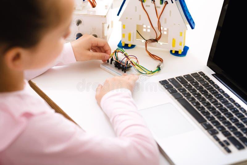 Robot de programación de la colegiala con el ordenador portátil en la lección imágenes de archivo libres de regalías