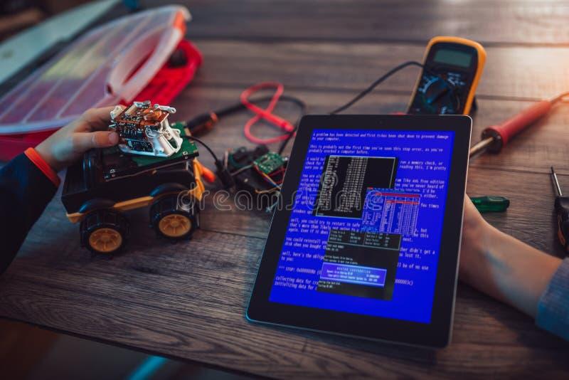 Robot de programación de los alumnos junto y usar la tableta digital imagenes de archivo