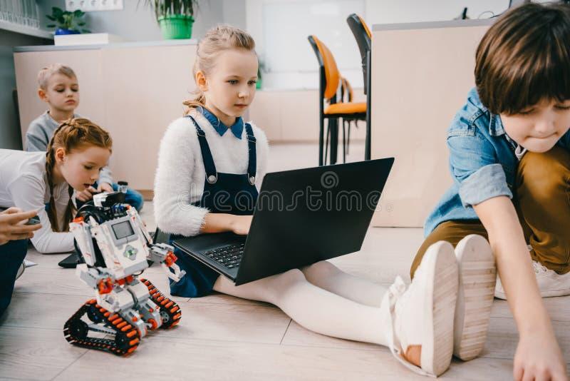 robot de programación de los niños mientras que se sienta en piso en el tronco foto de archivo