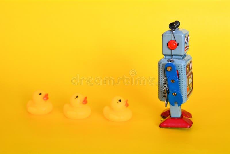 Robot del juguete de la lata del vintage y pequeños anadones aislados imágenes de archivo libres de regalías