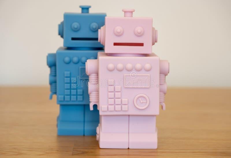 Robot del muchacho y de la muchacha - los niños juegan el banco biggy foto de archivo