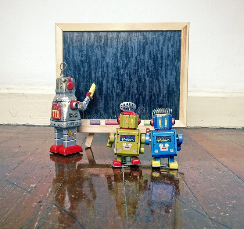 Robot en een blacboard op een houten vloer stock foto's