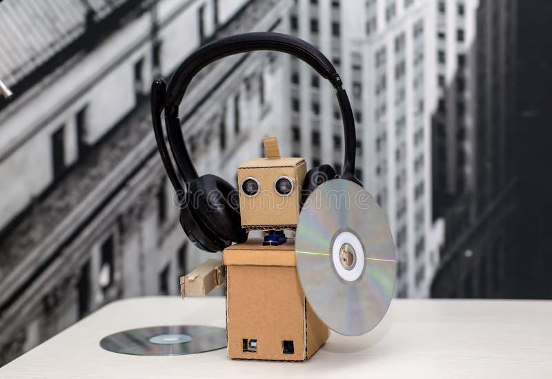 Robot en los auriculares que se sostienen en CD de la música del handsa fotos de archivo