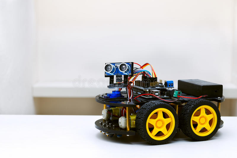 Robot with four wheels stands on a white table stock image