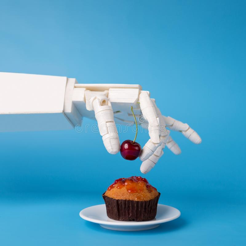Robot hand decorating sweet cupcake with fresh cherry royalty free stock photography
