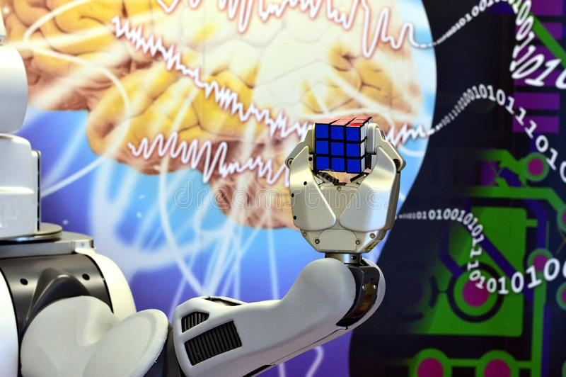 A robot hand holding a Rubik`s Cube with the abstract background. Of brain science and digital numbers. Londonderry / Derry, Northern Ireland, UK. Feb, 2017 stock photography