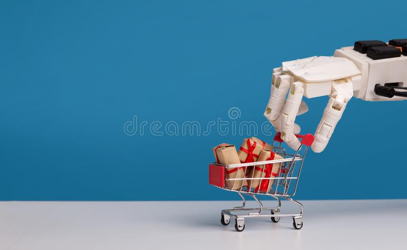Robot hand holding shopping cart with gift boxes stock images