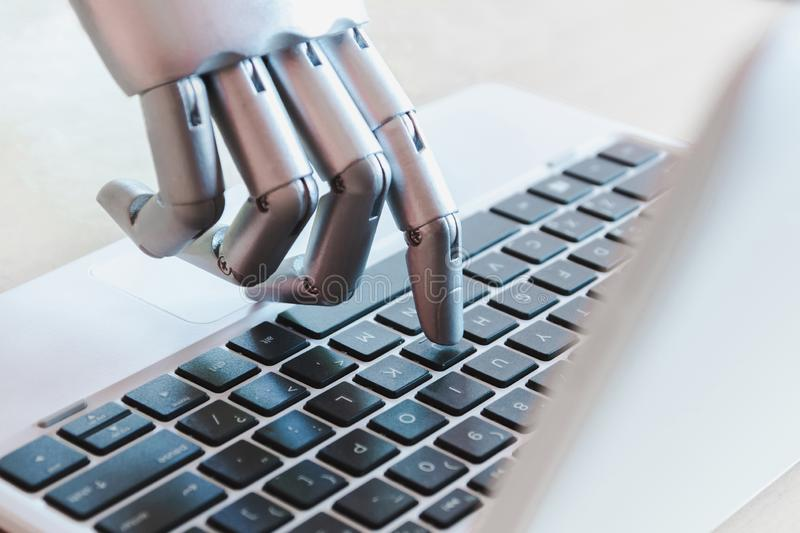 Robot hands and fingers point to laptop button advisor chatbot robotic artificial intelligence royalty free stock image
