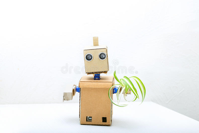 Robot with hands on the table and holding a green flower in his stock photography