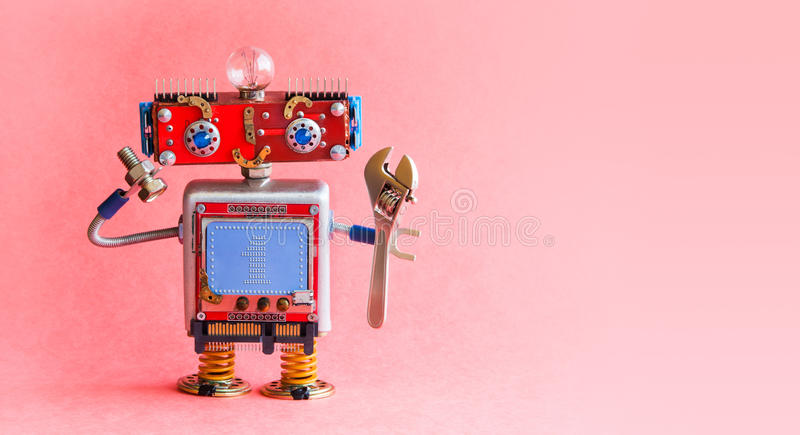 Robot handyman spanner wrench bolt nut in hands. Mechanical cyborg toy, red head, light bulb, monitor body text 1 on. Blue background. Automation robotic royalty free stock images