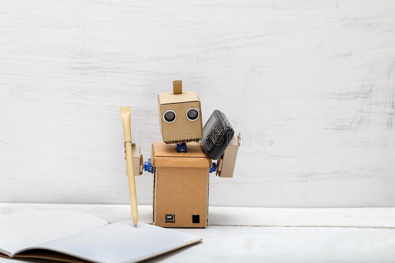 Robot holding a pen pen and talking on the phone royalty free stock images