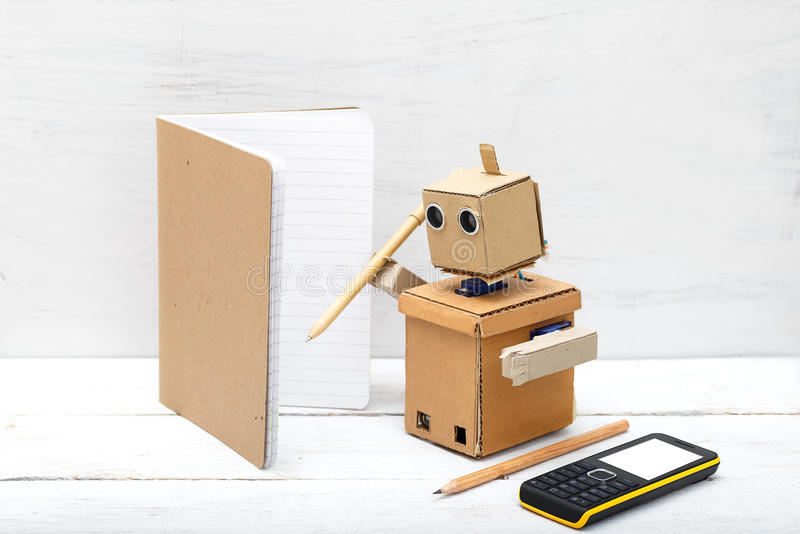 Robot holding a pen and writing in a notebook. Artificial Intelligence royalty free stock photography