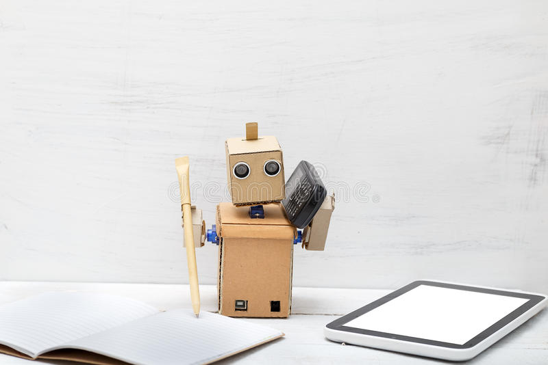 The robot holds a pen and the phone is near laptop. Work royalty free stock photography