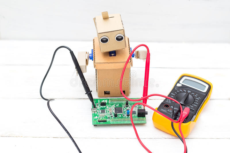 The robot holds a voltmeter in its hands and a printed circuit b royalty free stock images
