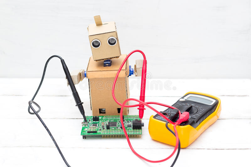 The robot holds a voltmeter in its hands and a printed circuit b royalty free stock image
