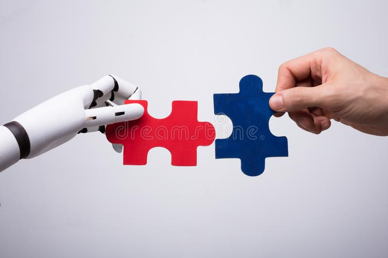 Robot And Human Hand Holding Jigsaw Puzzle stock photo