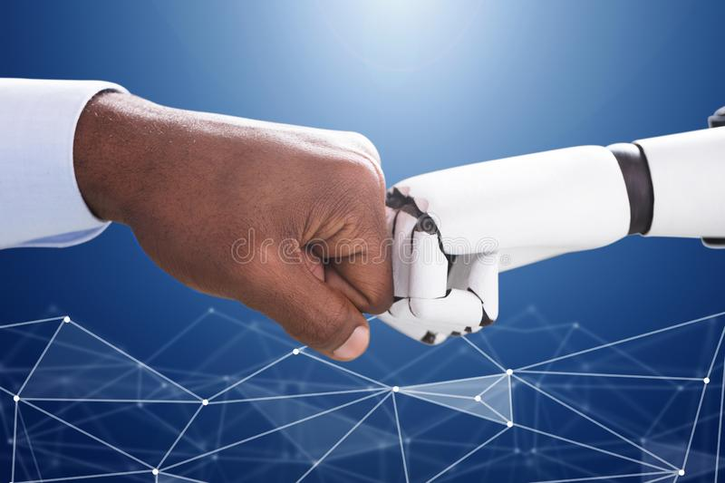Robot And Human Hand Making Fist Bump stock photography