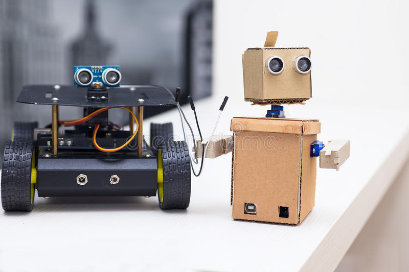Robot keeps wires and stands next to the other robot on a white table. Robot keeps wires and stands next to the other robot royalty free stock photo