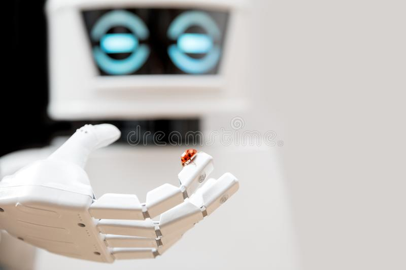 Robot with ladybug on his finger royalty free stock photo
