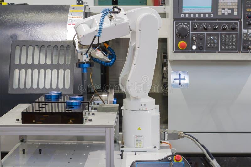 Robot mecánico de la mano que trabaja con la máquina del torno del CNC imagen de archivo libre de regalías