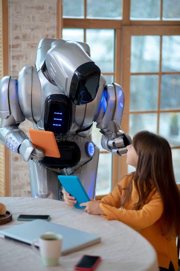 Robot med en tablett i handen och diskutera något med en tjej royaltyfri foto