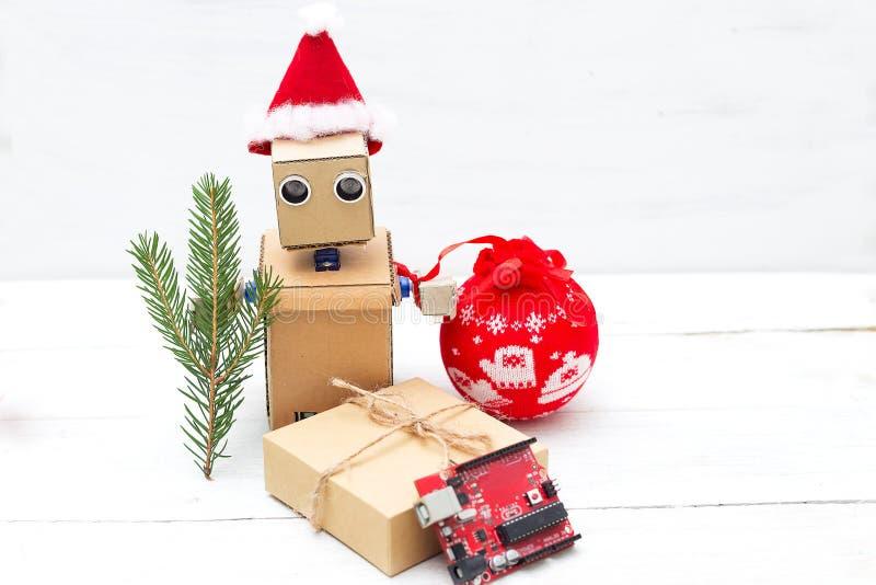 Robot med händer i jul hatt och juldecortion royaltyfria bilder