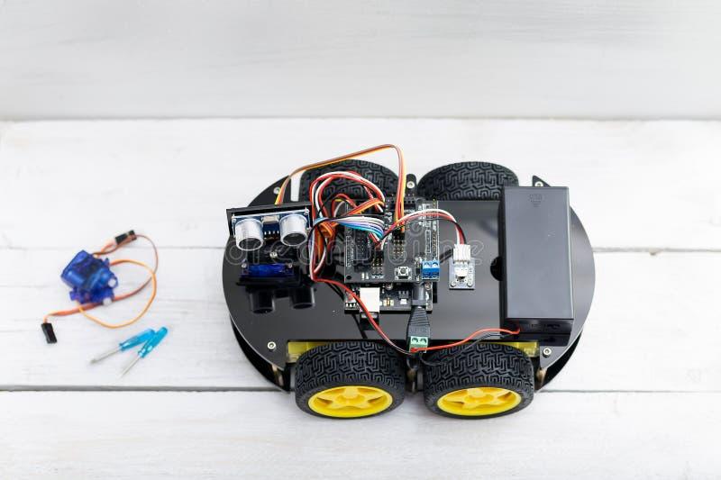 Robot på fyra hjul och ett antal två små skruvmejslar och arkivfoton